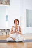 Meditación de la actitud de Lotus de la yoga en piso de madera Foto de archivo libre de regalías