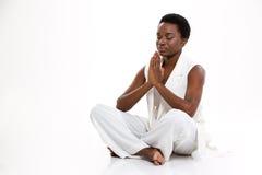 Meditando a jovem mulher afro-americano bonita que senta-se na ioga levante Fotos de Stock