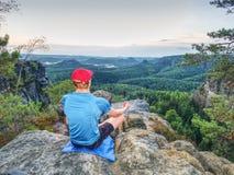 Meditando la posición de la yoga respecto al top de montañas El hombre meditate imagen de archivo libre de regalías