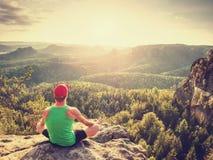 Meditando la posición de la yoga respecto al top de montañas El hombre meditate foto de archivo