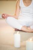 Meditando a mulher com velas iluminadas Fotografia de Stock Royalty Free