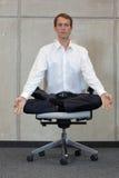 Meditando o homem de negócios caucasiano nos lótus levante na cadeira do escritório Fotos de Stock