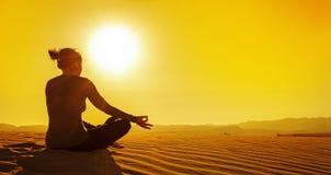 Meditando su duna di sabbia al tramonto Fotografie Stock