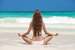 Meditação da mulher na praia tropical Imagens de Stock