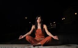 Meditação praticando da mulher bonita na noite Imagem de Stock