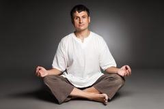 Meditar calmo do homem isolado sobre a obscuridade Imagem de Stock Royalty Free