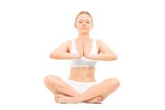 Meditar da jovem mulher assentado no assoalho Fotografia de Stock