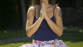 Meditar a la hembra de la yogui dobla las manos en namaste para expresar gratitud al universo almacen de metraje de vídeo