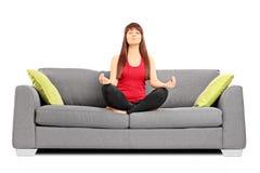 Meditar novo da fêmea assentado em um sofá Fotografia de Stock Royalty Free