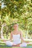 Meditare di seduta della donna calma su stuoia di esercizio Fotografia Stock Libera da Diritti