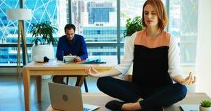 Meditare esecutivo femminile al suo scrittorio stock footage