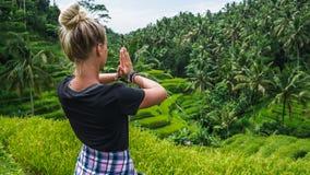 Meditare femminile su terrazzo del riso di Tegalalang, Ubud, Bali, Indonesia fotografie stock libere da diritti