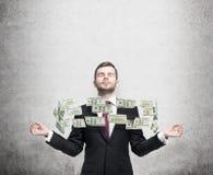 Meditare uomo e pilotare le note del dollaro fra le sue mani Fondo concreto Fotografie Stock