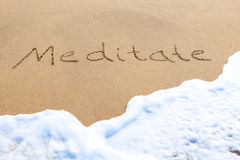 Meditate - escrito en la arena Imagen de archivo libre de regalías