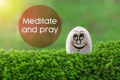 Meditate and pray. The text meditate and pray with gratitude with stone smile happy face on green moss and sunshine light background royalty free stock photos
