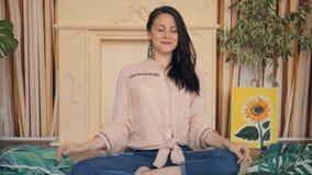 meditatie Een leuk meisje zit op een tapijt in een lotusbloem stelt stock footage