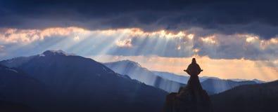 Meditatie in een yogapositie inzake de bovenkant van berg Stock Afbeelding