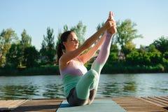 Meditatie en yoga het praktizeren bij zonsondergang Jonge vrouw die yoga in ochtendpark doen dichtbij meer stock afbeelding