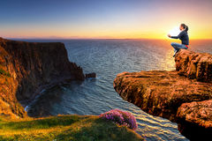 Meditatie op de rand van een klip bij zonsondergang Stock Foto's