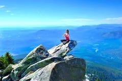 Meditatie op rots met bergen en valleimeningen royalty-vrije stock afbeelding