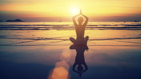 Meditatiemeisje op de achtergrond van het overweldigende overzees en de zonsondergang Royalty-vrije Stock Foto's