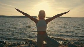 Meditatiemeisje op het overzees tijdens zonsondergang Geschiktheid en gezonde levensstijl De praktijk van de yoga stock video