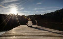Meditating σε έναν λιμενοβραχίονα στο ηλιοβασίλεμα Στοκ Φωτογραφίες