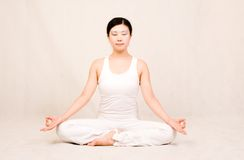 Meditating. A asian Chinese girl doing yoga exericise indoors Royalty Free Stock Photo
