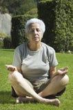 Meditating. Senior woman meditating at the park Royalty Free Stock Image