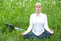 Meditating. Portrait of meditating woman sitting on meadow in summer during break Stock Images