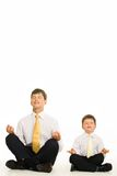 Meditating. Image of man and boy meditating in studio over white background Stock Images