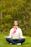 Meditating. Portrait of calm girl meditating outside in autumn Royalty Free Stock Photo