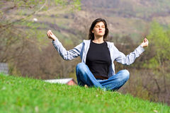 Meditating. Young woman meditating royalty free stock image