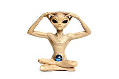 Meditating alien. Alien meditating with hands on his head and legs crossed Royalty Free Stock Images