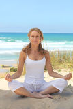Meditating on the beach Royalty Free Stock Photo