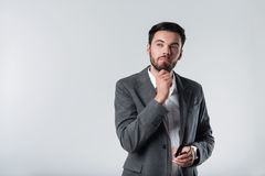 Meditating bearded man standing against white background. Stock Image