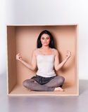 Meditating woman trapped in box concept Stock Photo