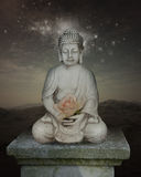 Meditating buddha statue. With rose and stars in the background Royalty Free Stock Photo