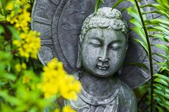Meditating Buddha in a Zen Garden. Buddha peacefully surrounded by nature positive energy doing his meditation royalty free stock photo