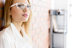 Meditating business woman standing in office. Time for thoughts. Portrait of charming young lady in glasses. She looking aside while resting after work. Copy Royalty Free Stock Photo