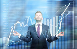 Meditating businessman and chart. Meditating businessman with business chart and blurry city view in the background Royalty Free Stock Image
