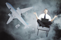 Meditating businessman falling out or airplane. Meditating man with laptop falling out of airplane on night sky background stock photos