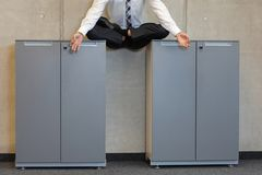 Meditating businessman in lotus pose on cabinets in office Stock Photo