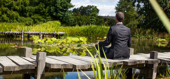 Meditating businessman relaxing on wooden path above water Royalty Free Stock Images