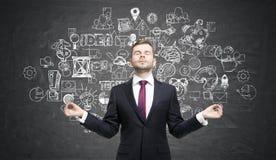 Meditating businessman wearing a red tie near chalkboard with bu Royalty Free Stock Photos