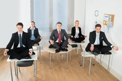 Meditating businesspeople sitting on desk Stock Images