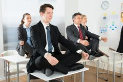 Meditating businesspeople sitting on desk Stock Image