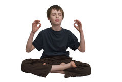 Meditating child. An isolated image of a child sitting in the meditation position royalty free stock images