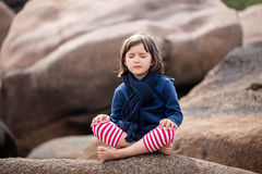 Meditating child with eyes closed sitting, relaxing for yoga exercise. Meditating little child with eyes closed sitting in a granite stone nature, relaxing and stock photo