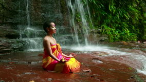 Meditating with Facial Painting in borneo rainforest waterfall stock footage